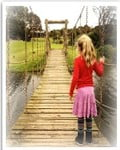 young girl standing on a bridge