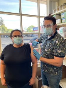 Phil Hauser of Hauser's pharmacy in Dunnville looking at the camera while administering a COVID-19 vaccine to a female unnamed patient. Phil is wearing a bright shirt and personal protective equipment. Both are wearing masks.