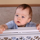 baby on the other side of a baby gate